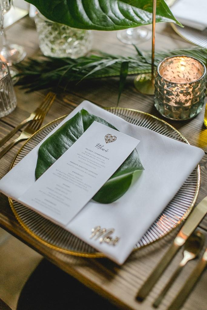 Hochzeitsgedeck mit Gold Akzenten und grünem Palmenblatt | Hochzeitsfoto: Hanna Witte