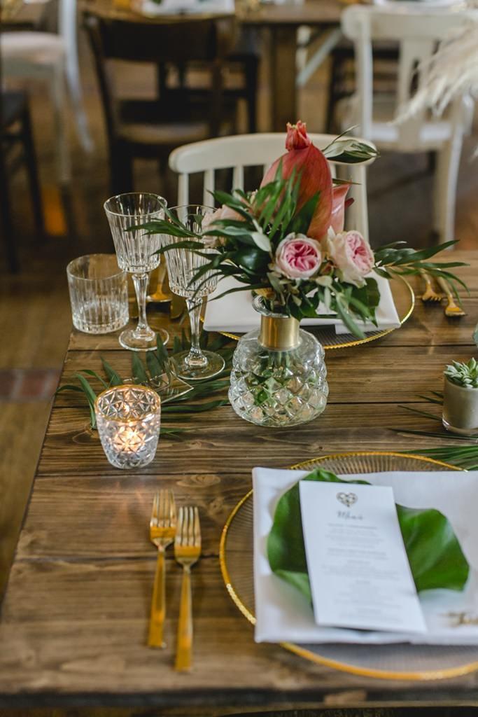Hochzeitstischdeko mit Goldbesteck, Palmenblättern und rosafarbenen Blumen | Hochzeitsfoto: Hanna Witte
