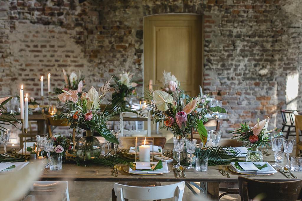 Hochzeitslocation Rittergut Orr: Festlich gedeckte Tische mit Greenery, Flamingoblumen und Protea | Hochzeitsfoto: Hanna Witte
