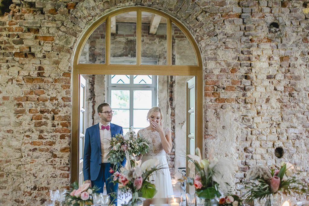 das Brautpaar sieht zum ersten Mal den hübsch dekorierten Festsaal im Rittergut Orr | Hochzeitsfoto: Hanna Witte