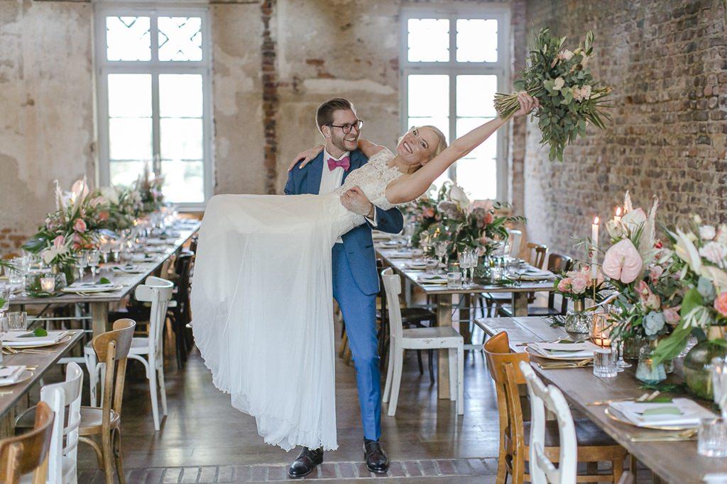 der Bräutigam trägt die Braut im Festsaal von Rittergut Orr auf Händen | Hochzeitsfoto: Hanna Witte