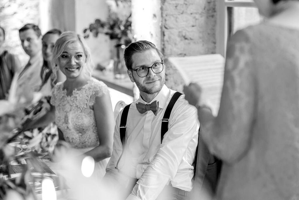 das Brautpaar während einer Rede auf der Hochzeitsfeier | Hochzeitsfoto: Hanna Witte