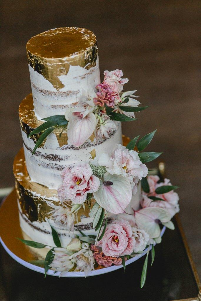 Undone Hochzeitstorte mit Blattgold und Blumen in hellem Rosa | Hochzeitsfoto: Hanna Witte