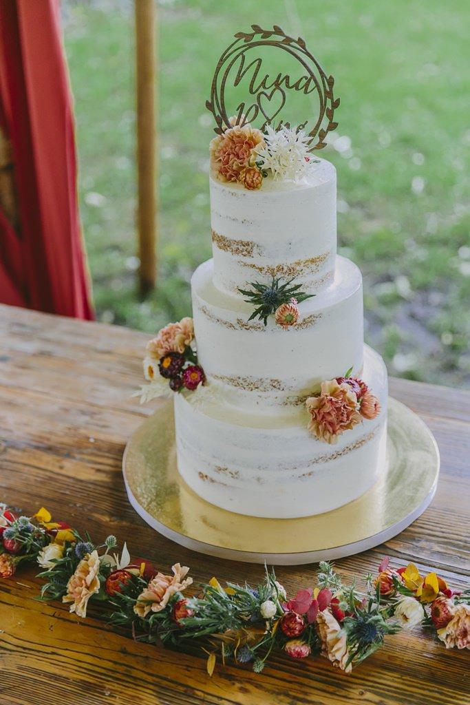 Schlichte Semi Naked Cake Hochzeitstorte mit Blumendeko in Herbstfarben | Foto: Hanna Witte