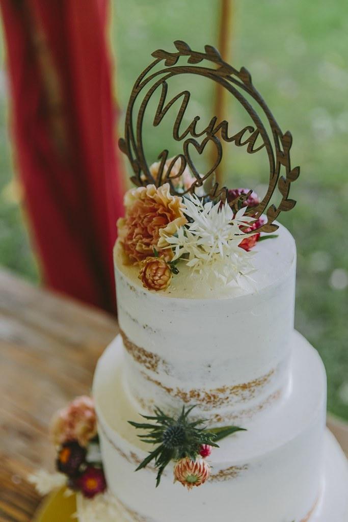 Undone Hochzeitstorte mit Blütendeko und personalisiertem Cake Topper | Foto: Hanna Witte