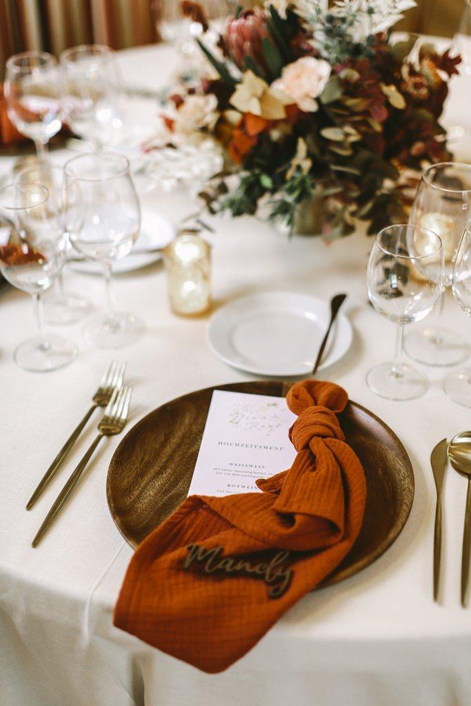 Herbstliche Hochzeitstischdeko mit Platzteller aus Holz, goldenes Besteck und Stoffserviette in Orange | Foto: Hanna Witte