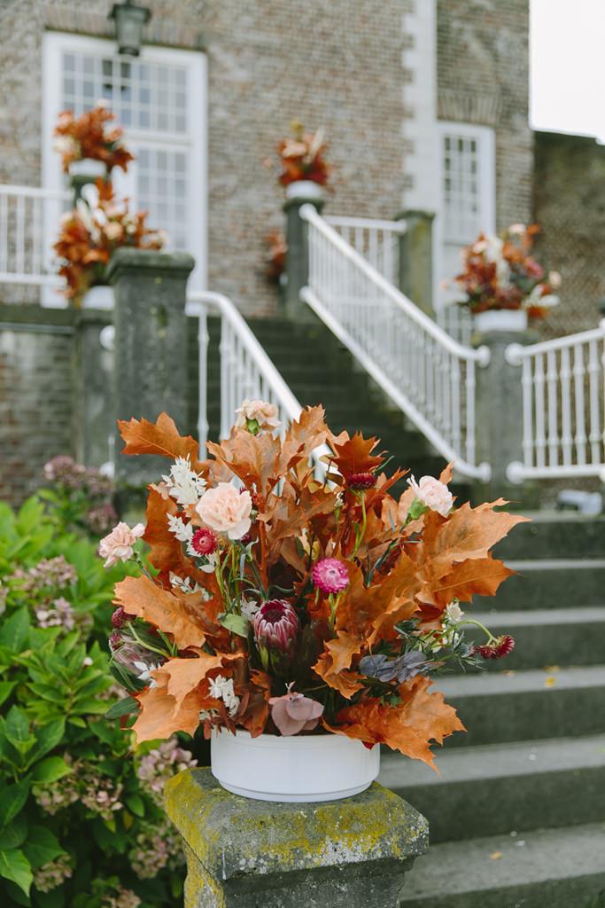 Herbstliche Blumendeko an der Treppe zu der Hochzeitslocation Schloss Hertefeld | Foto: Hanna Witte