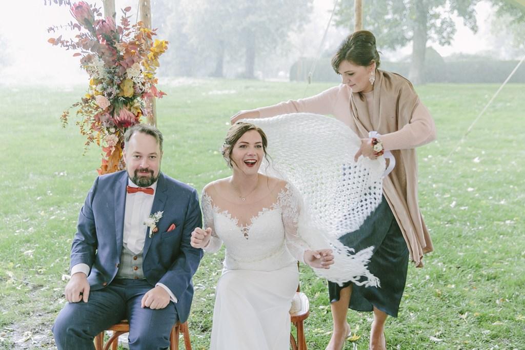 das Brautpaar lacht während der Regen bei der Trauung einsetzt | Foto: Hanna Witte