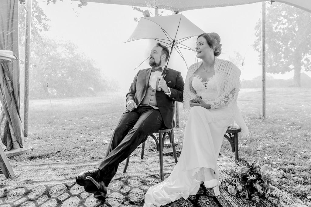 das Brautpaar schützt sich mit einem Schirm vor dem Regen | Foto: Hanna Witte