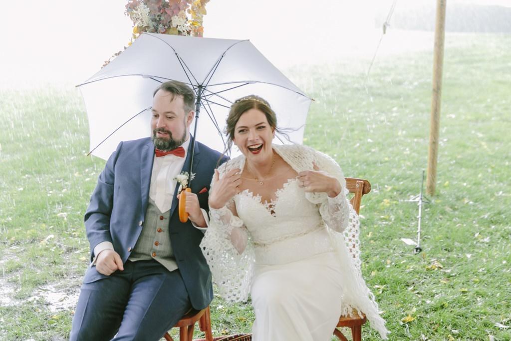 das Brautpaar lacht während ihrer Trauung im strömenden Regen | Foto: Hanna Witte