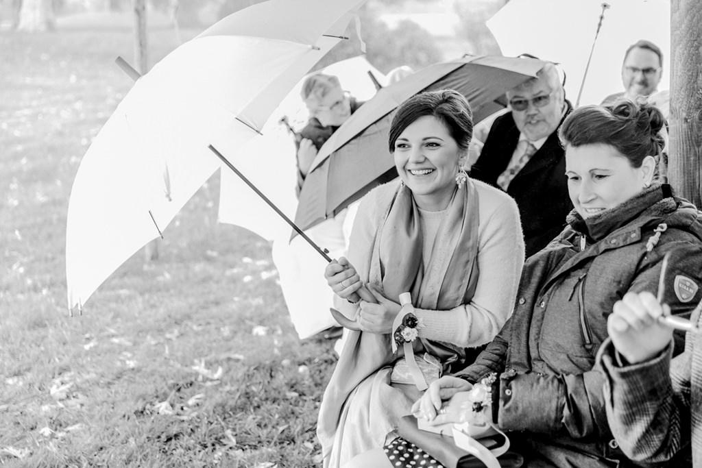 die Hochzeitsgäste schützen sich mit Regenschirmen vor dem Regen | Foto: Hanna Witte