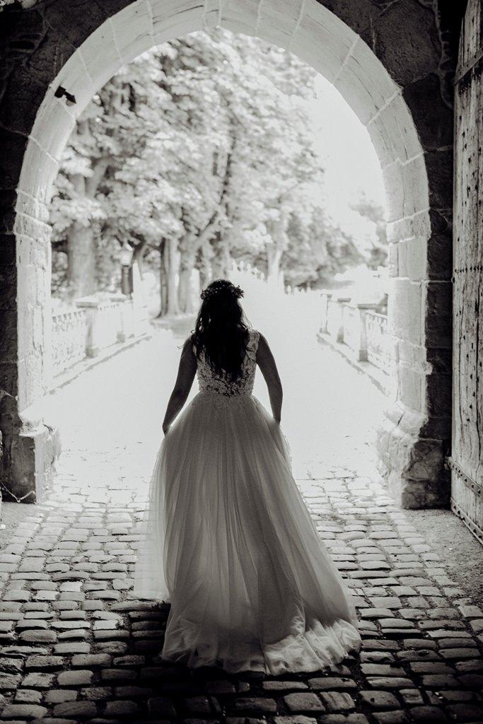 Hochzeitsfotografie im Regen: Die Braut läuft durch einen Torbogen   Foto: Hanna Witte