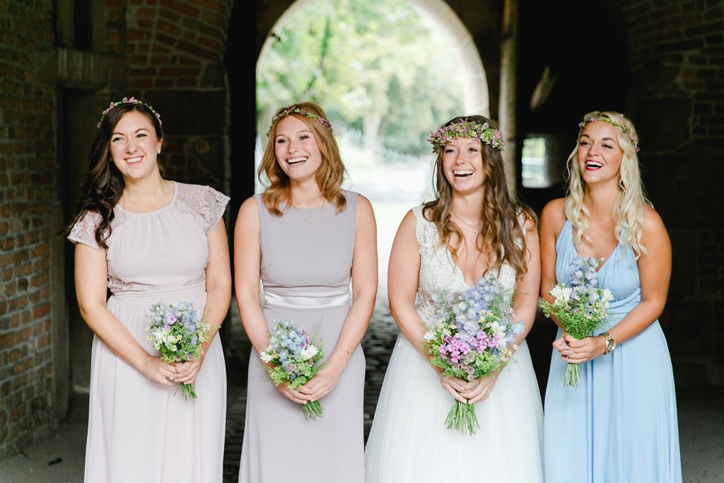 Hochzeitsbild im Regen: Braut und Brautjungfern stehen in einem Torbogen | Foto: Hanna Witte