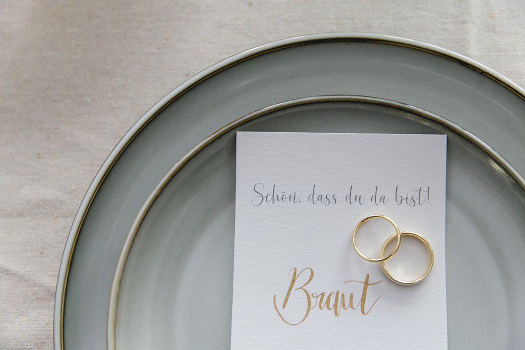 die goldenen Trauringe liegen auf dem Namensschild der Braut   Foto: Hanna Witte