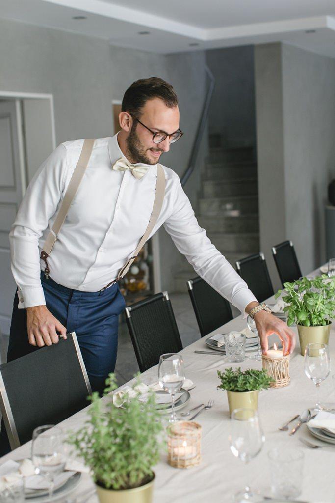 der Bräutigam arrangiert die Kerzen auf dem gedeckten Hochzeitstisch   Foto: Hanna Witte