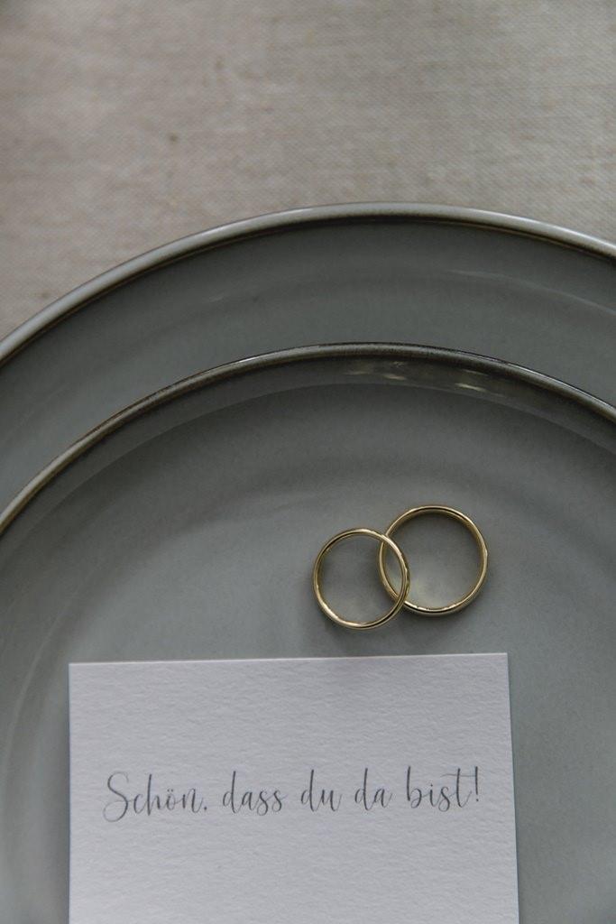 goldene Eheringe liegen mit einer Spruchkarte auf einem Teller   Foto: Hanna Witte