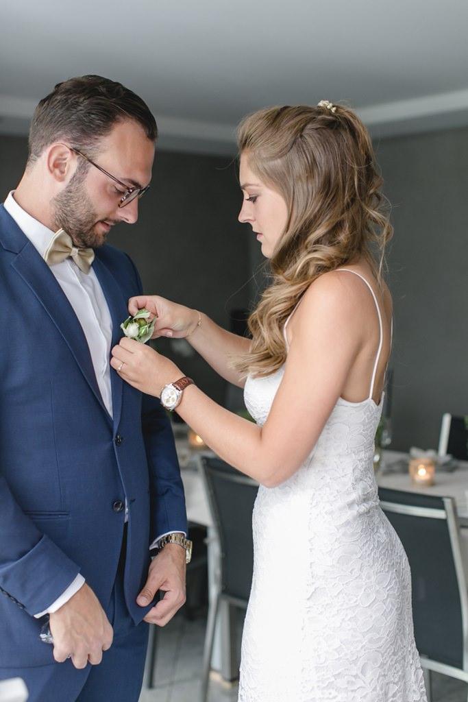 die Braut befestigt die Boutonniere am Anzug des Bräutigams   Foto: Hanna Witte