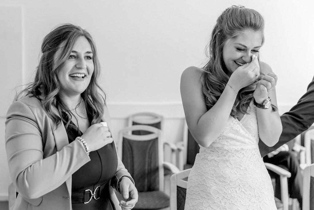 Braut und Trauzeugin wischen sich während der standesamtlichen Trauung ihre Tränen weg   Foto: Hanna Witte