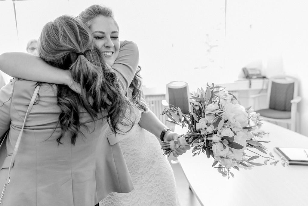 die Braut wird nach der standesamtlichen Hochzeit von ihrer Trauzeugin umarmt   Foto: Hanna Witte