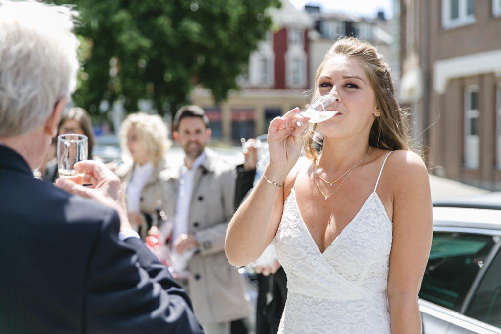 die Braut gönnt sich nach der standesamtlichen Hochzeit ein Glas Sekt   Foto: Hanna Witte