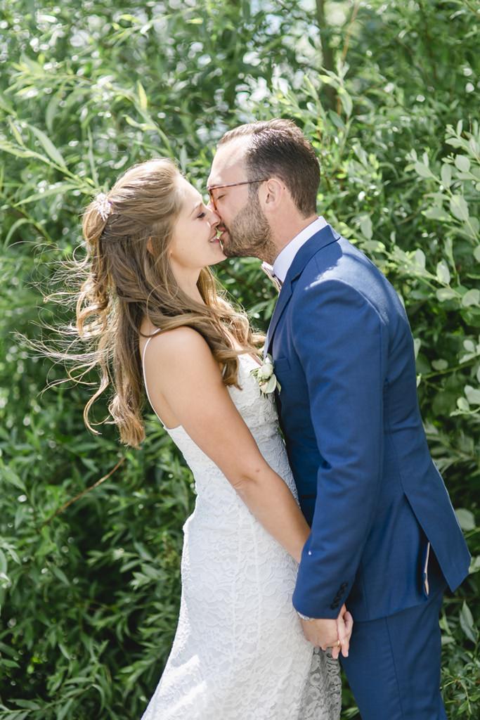 das Brautpaar küsst sich beim Paarshooting im Grünen   Foto: Hanna Witte