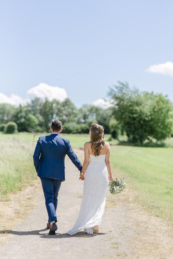 Braut und Bräutigam laufen Hand in Hand auf einem Feldweg   Foto: Hanna Witte