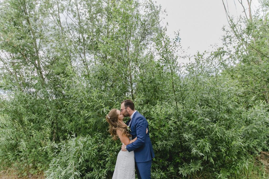 das Brautpaar küsst sich vor grüner Naturkulisse   Foto: Hanna Witte