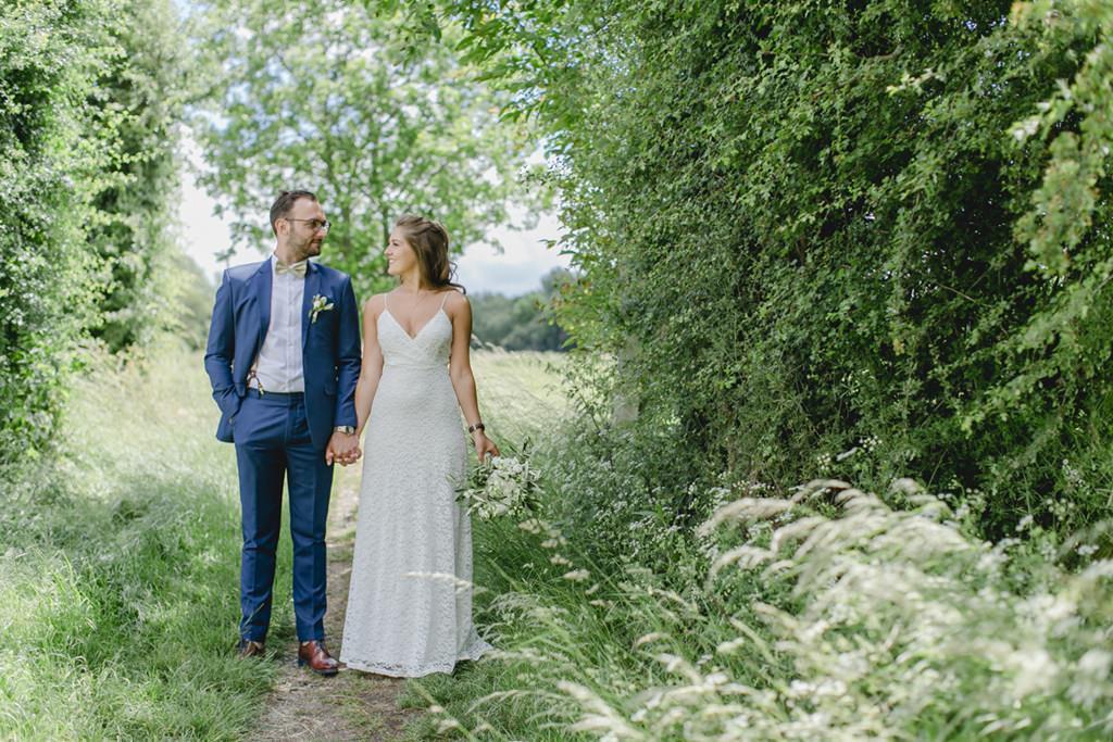 Paarfoto von Braut und Bräutigam auf einem Feldweg im Grünen   Foto: Hanna Witte