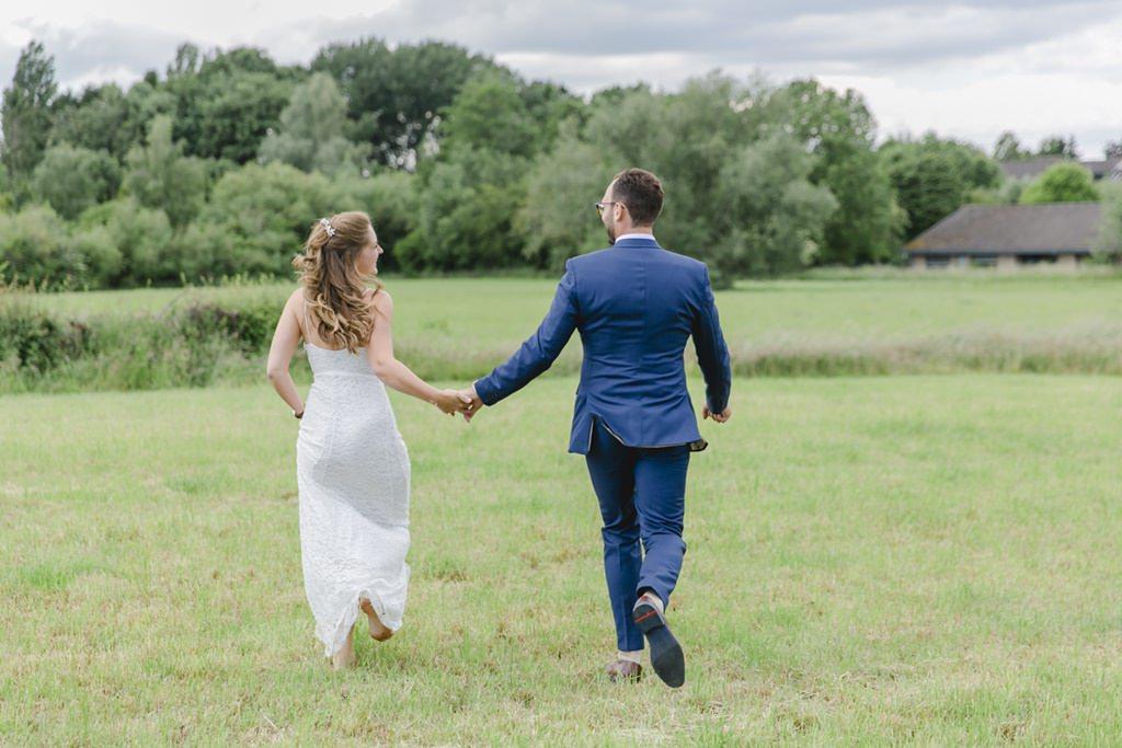 das Brautpaar läuft fürs Hochzeitsfoto über eine Wiese   Foto: Hanna Witte