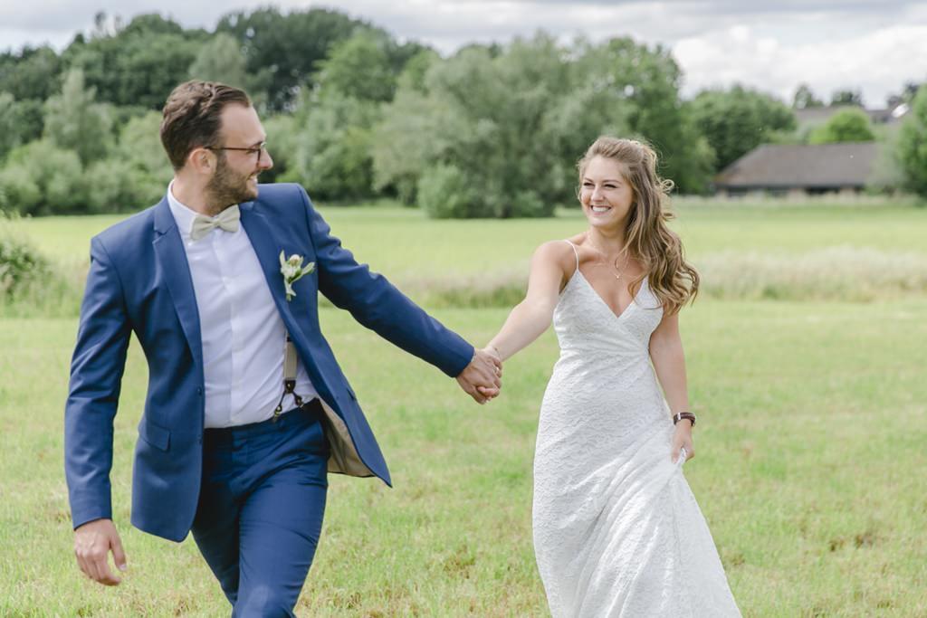 das Brautpaar geht strahlend Hand in Hand über eine Wiese   Foto: Hanna Witte