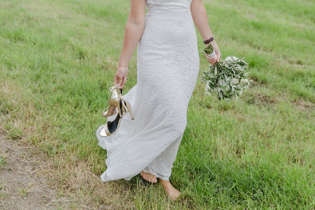 Hochzeitsfoto von der Braut wie sie barfuss über eine Wiese geht   Foto: Hanna Witte